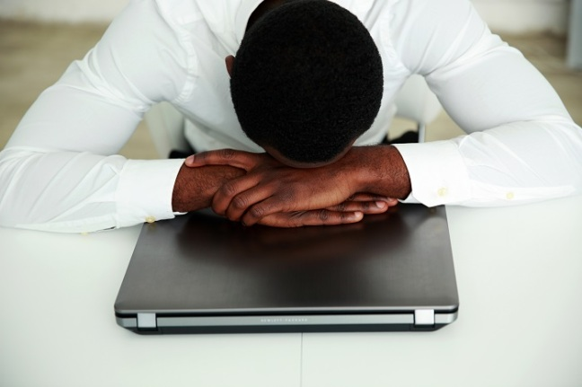 African man sleeping at his workplace in office